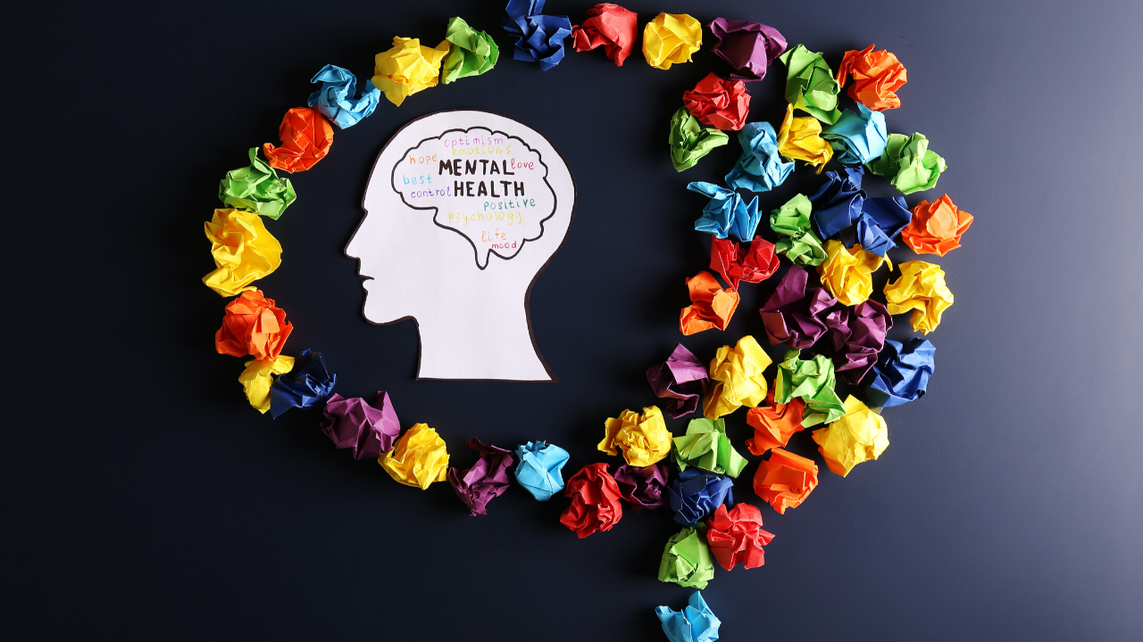 Various colored pieces of paper are crumpled up in the shape of a brain, and in the middle is a paper cut out of a person's head, with words that symbolize psychological capital and emotional intelligence.