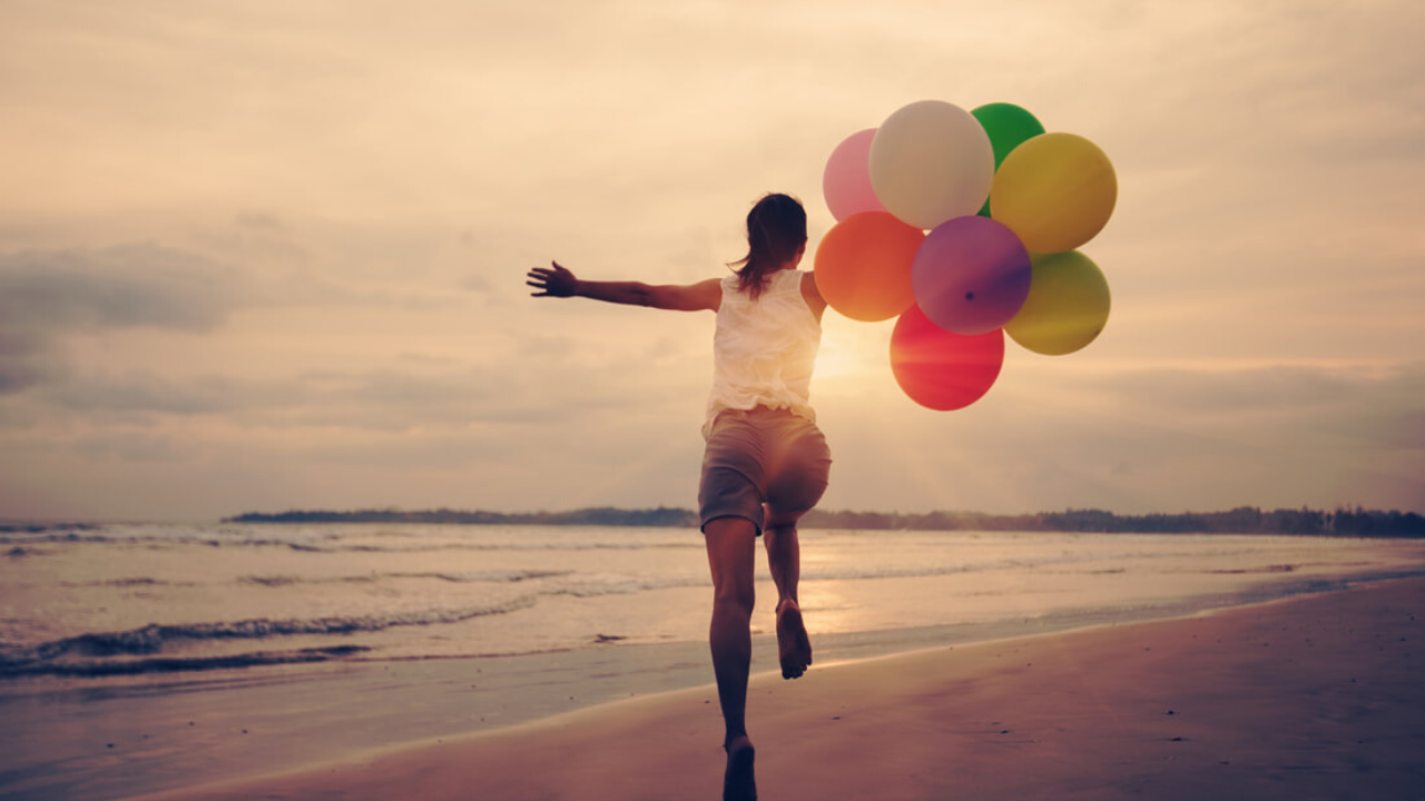 A woman runs on a beach with colorful balloons. She's clearly having fun!