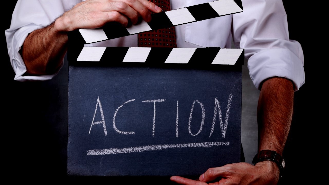 A man holds a movie set action sign that reads