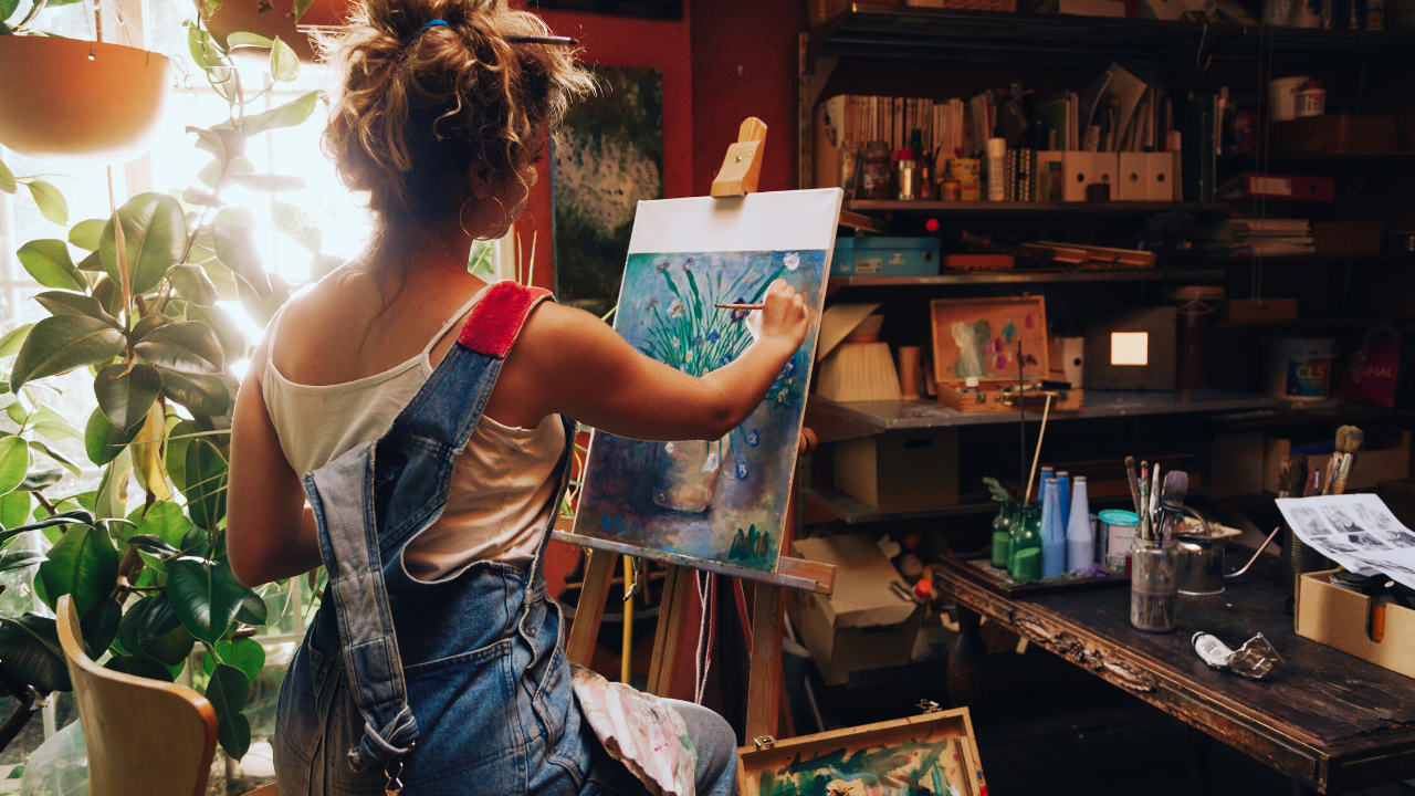 A person sits in a studio and paints a vase and flowers on a canvas.