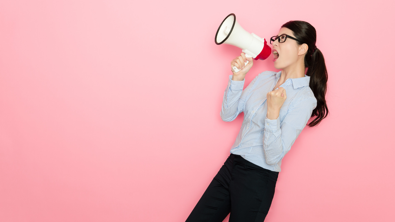 A woman yells into a megaphone. There must be a better way to communicate!